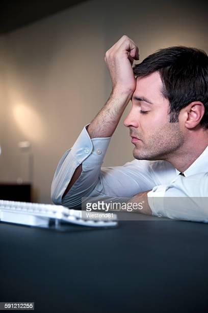 Overworked businessman leaning on desk