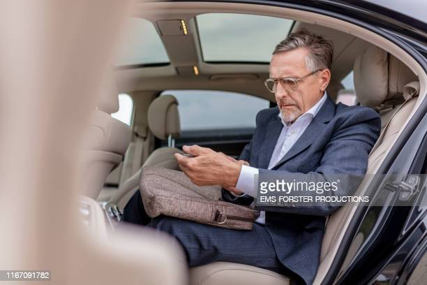 overworked businessman sitting on back seat in car and using mobile phone - limousine stock pictures, royalty-free photos & images