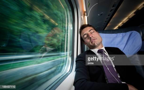 働きすぎのビジネスマン寝室とリスニング音楽の窓のそばにトレーン