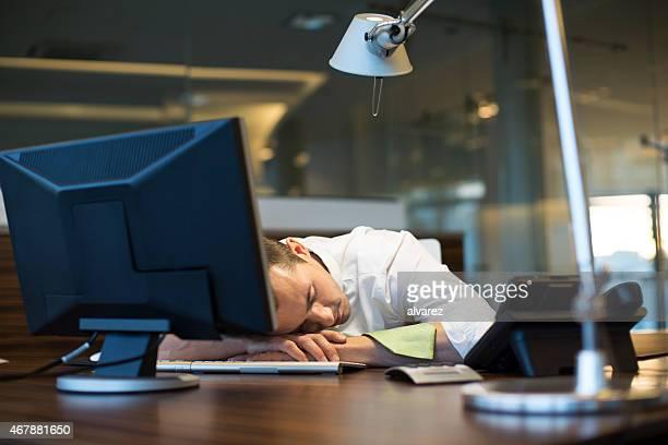 Overworked businessman sleeping at his desk