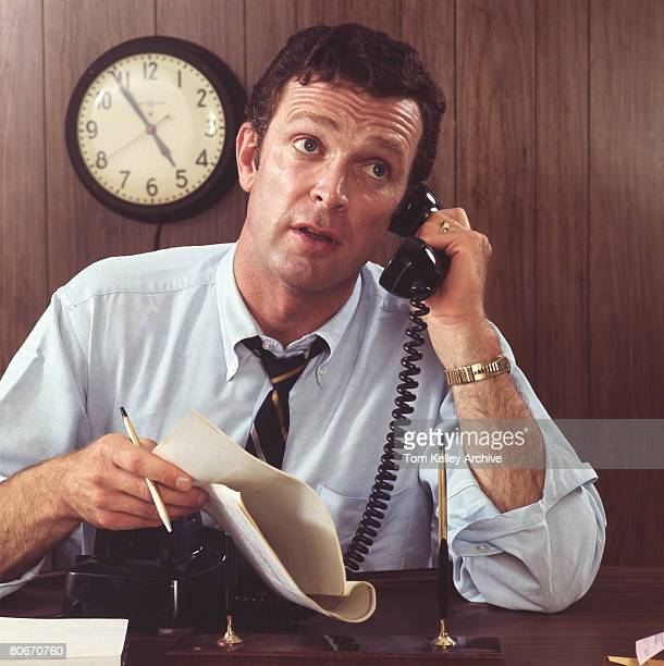 Overworked businessman talking on phone at desk in woodpaneled office near the end of the workday mid1970s