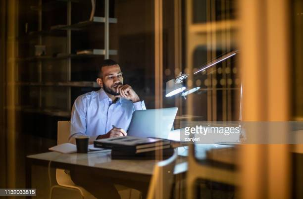 overworked businessman working late in the office - financial occupation stock pictures, royalty-free photos & images