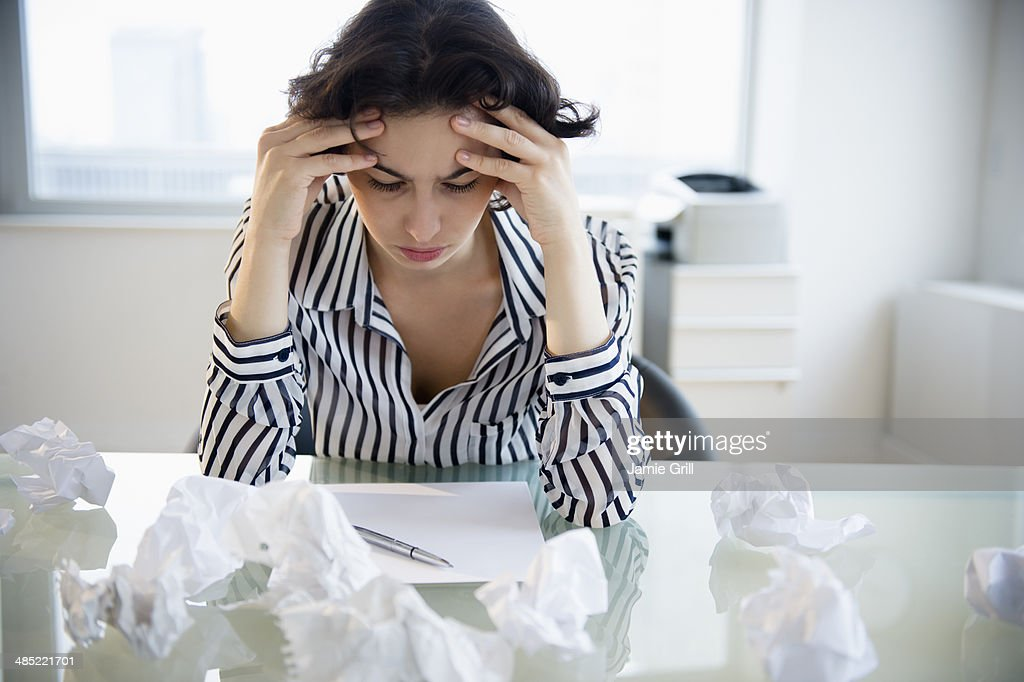 Overworked businesswoman sitting at desk : Stock Photo