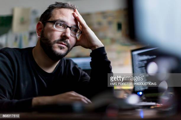 overworked computer programmer in his home office
