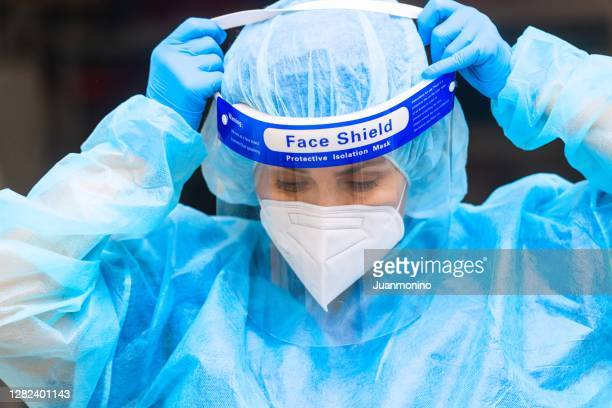 overworked, female mature health care worker putting on a protection workwear - protective workwear stock pictures, royalty-free photos & images