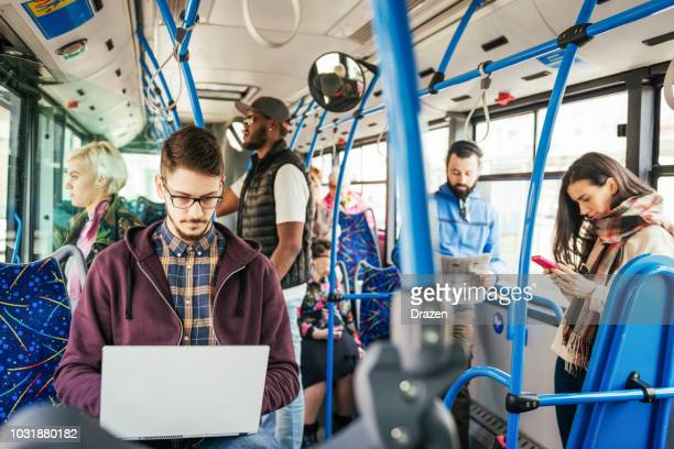 overworked freelancer working on laptop in public bus - vehicle interior stock pictures, royalty-free photos & images