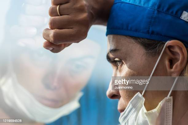 overworked healthcare worker looking through a window, very concerned, very tired - overworked stock pictures, royalty-free photos & images