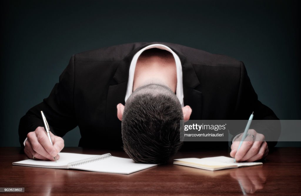 Overworked man collapses while writing : Stock Photo