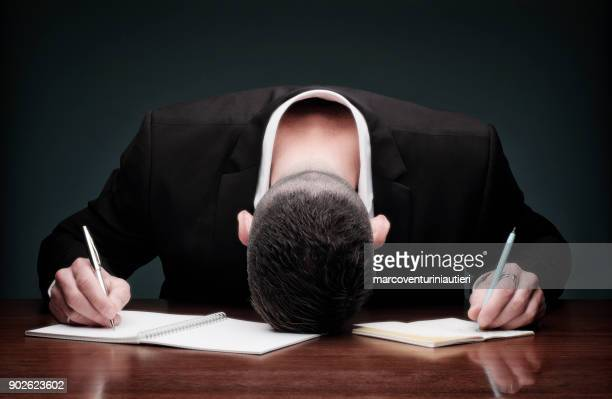 overworked man collapses while writing - collapsing stock pictures, royalty-free photos & images