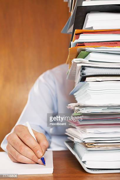 Overworked Man Writing Behind Stack of Files