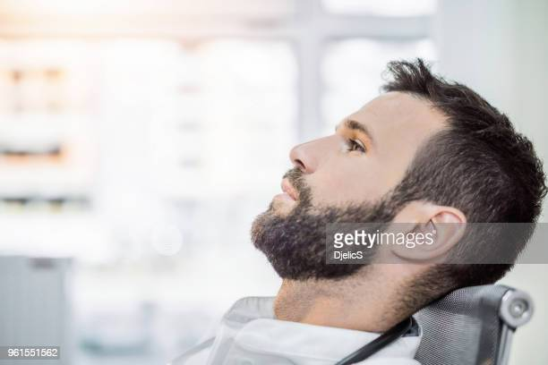 Overwerkt mid volwassen mannelijke gezondheidszorg werknemer met een veel gaande is in zijn geest.