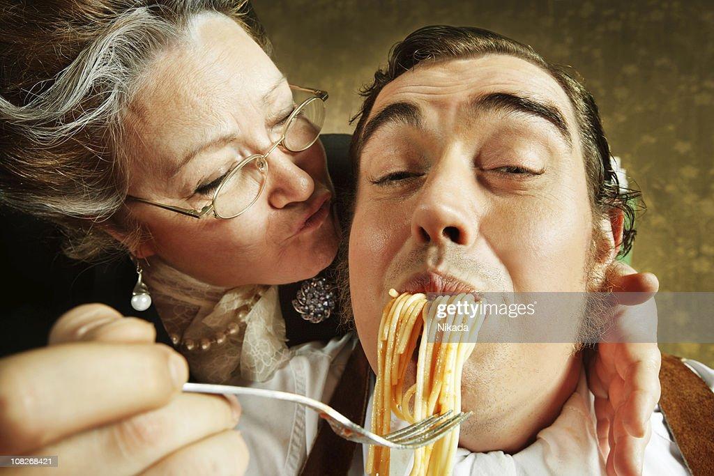 Overzealous Mother Feeding Adult Son Pasta : Stock Photo