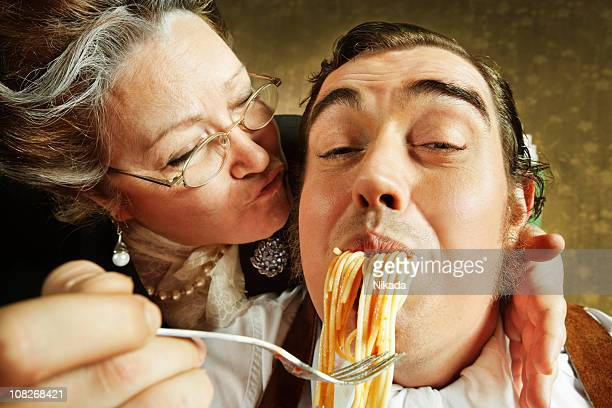 Overzealous Mother Feeding Adult Son Pasta