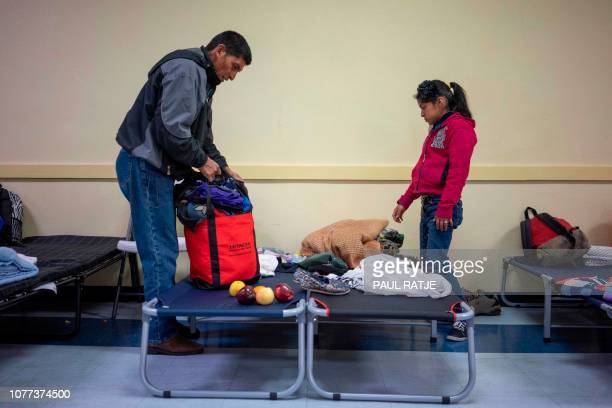 Ovidio Lopez Tum and his daughter Ingrid Maribel pack up their belongings for their trip the following day at the church hall of the Basilica of San...
