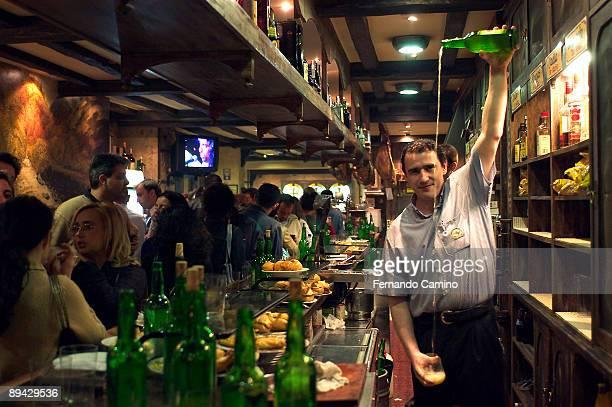 Oviedo, Asturias. Spain. A barman pouring out a glass of cider.