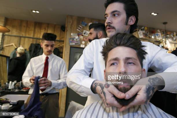 Owain Jones, lifestyle blogger, has his beard groomed by barber Fabio Marques during a launch event for House 99, a grooming brand for men created by...