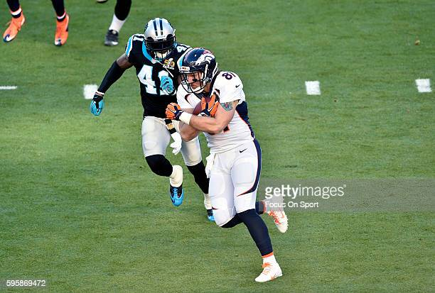 Owen Daniels of the Denver Broncos runs with the ball pursued by Roman Harper of the Carolina Panthers during Super Bowl 50 at Levi's Stadium on...