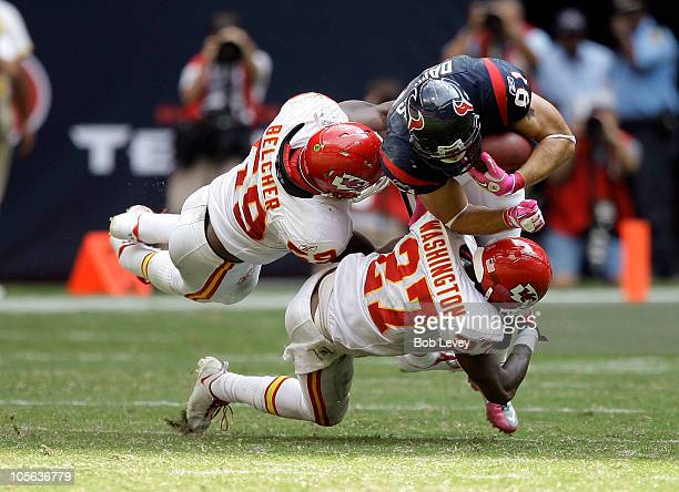 Owen Daniels of the Houston Texans is tackled by linebacker Jovan Belcher and cornerback Donald Washington of the Kansas City Chiefs at Reliant...