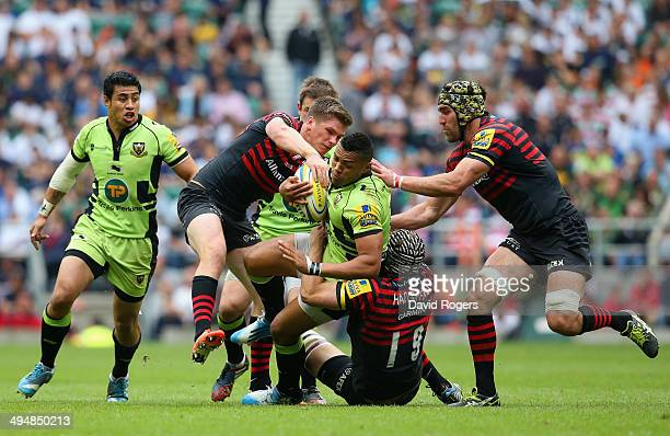 Owen Farrell and Alistair Hargreaves of Saracens tackle Luther Burrell of Northampton Saints during the Aviva Premiership Final between Saracens and...
