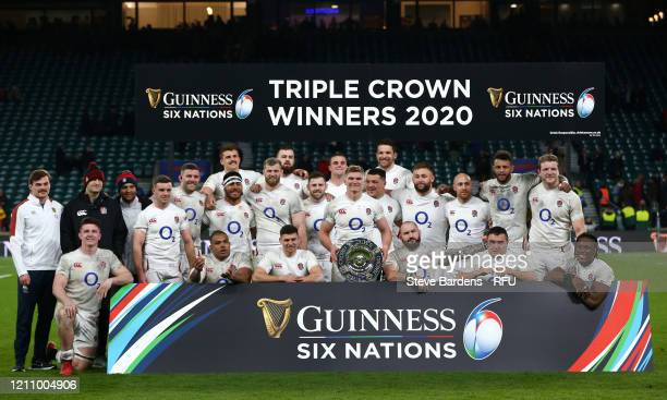 Owen Farrell and teammates celebrate with the Triple Crown Trophy following their victory in the 2020 Guinness Six Nations match between England and...