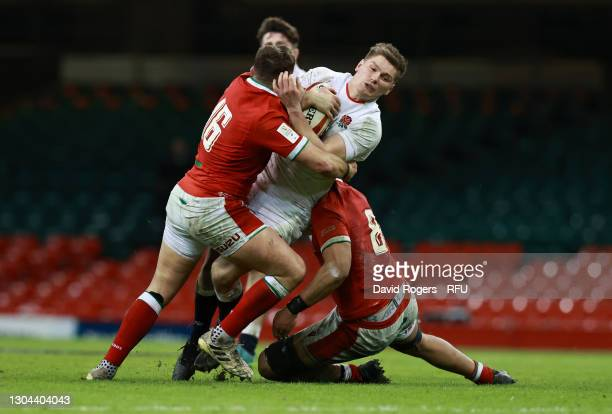 Owen Farrell of England is tackled by Elliot Dee and Taulupe Faletau of Wales during the Guinness Six Nations match between Wales and England at...