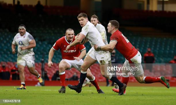 Owen Farrell of England is tackled by George North during the Guinness Six Nations match between Wales and England at Principality Stadium on...