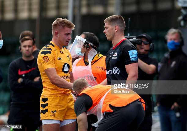 Owen Farrell of Saracens apologises to Charlie Atkinson of Wasps after being sent off for a previous tackle on him during the Gallagher Premiership...