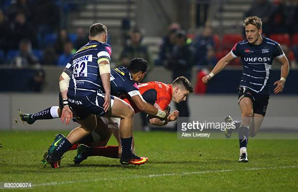 Owen Farrell of Saracens holds off a challenge from Denny Solomona of Sale Sharks to dive over the line to score the opening try during the European...