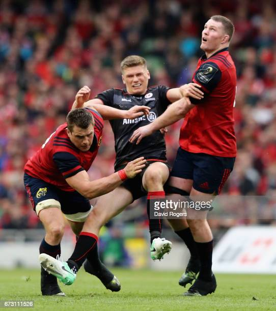 Owen Farrell of Saracens is stopped by CJ Stander and Donnacha Ryan during the European Rugby Champions Cup semi final match between Munster and...