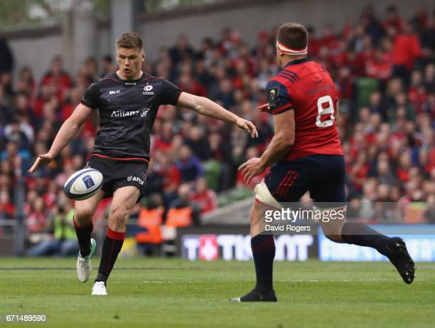 Owen Farrell of Saracens kicks past CJ Stander during the European Rugby Champions Cup semi final match between Munster and Saracens at the Aviva...