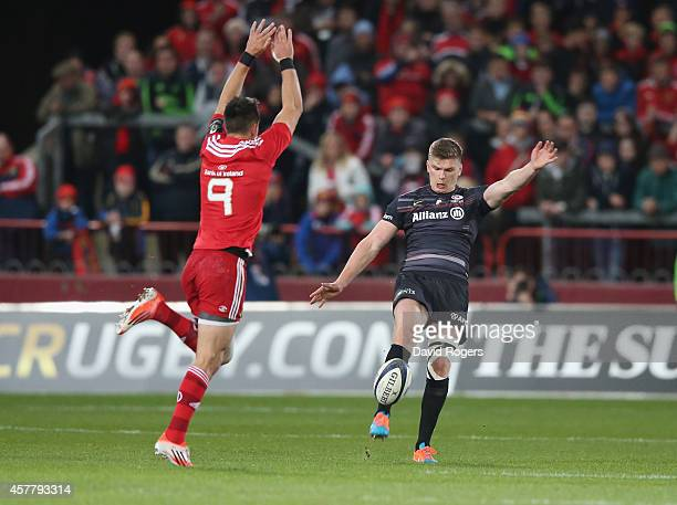 Owen Farrell of Saracens kicks the ball upfield past Conor Murray during the European Rugby Champions Cup match between Munster and Saracens at...