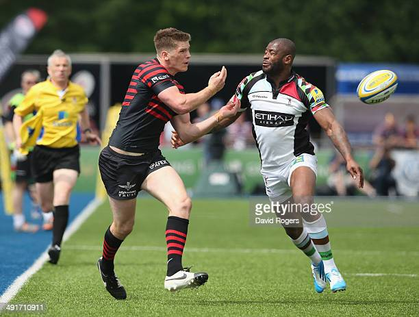 Owen Farrell of Saracens passes the ball as Ugo Monye looks on during the Aviva Premiership semi final match between Saracens and Harlequins at...