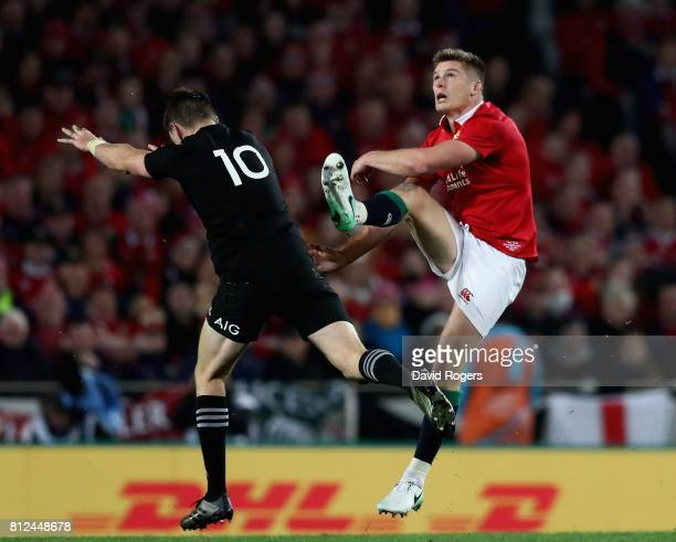 Owen Farrell of the Lions kicks the ball past Beauden Barrett during the Test match between the New Zealand All Blacks and the British Irish Lions at...