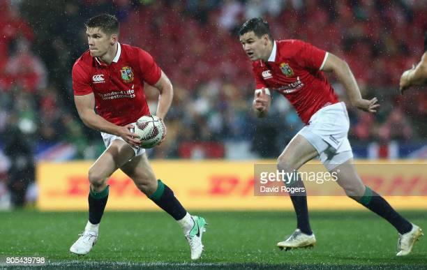 Owen Farrell of the Lions runs with the ball with Jonathan Sexton in support during the match between the New Zealand All Blacks and the British...