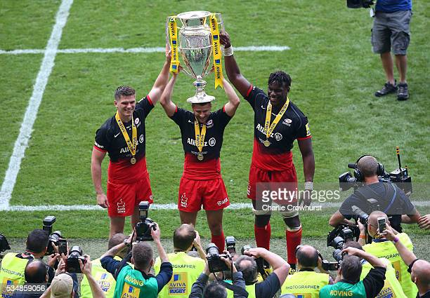Owen Farrell Richard Wigglesworth and Maro Itoje of Saracens celebrate with the trophy after victory in the Aviva Premiership final match between...