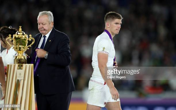 Owen Farrell the England captain looks dejected as he walks past World Rugby chairman Sir Bill Beaumont after their defeat during the Rugby World Cup...