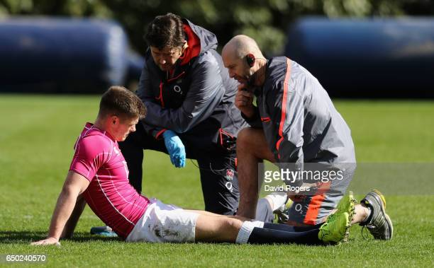 Owen Farrell the England centre receives attention from England physio Phil Pask and Rob Young the team doctor during the England training session...
