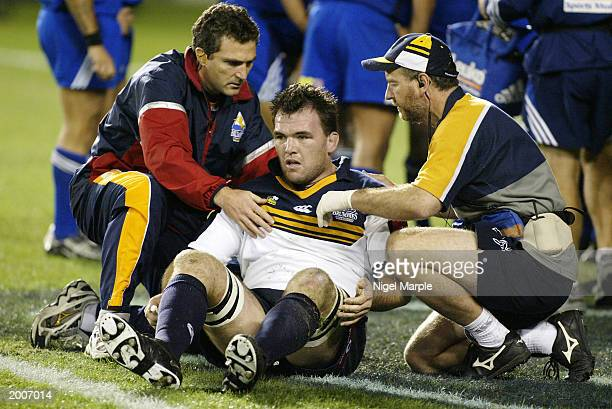 Owen Finegan of the Brumbies is attended by medical staff after scoring a try and banging his head in the process during the Super 12 semifinal game...