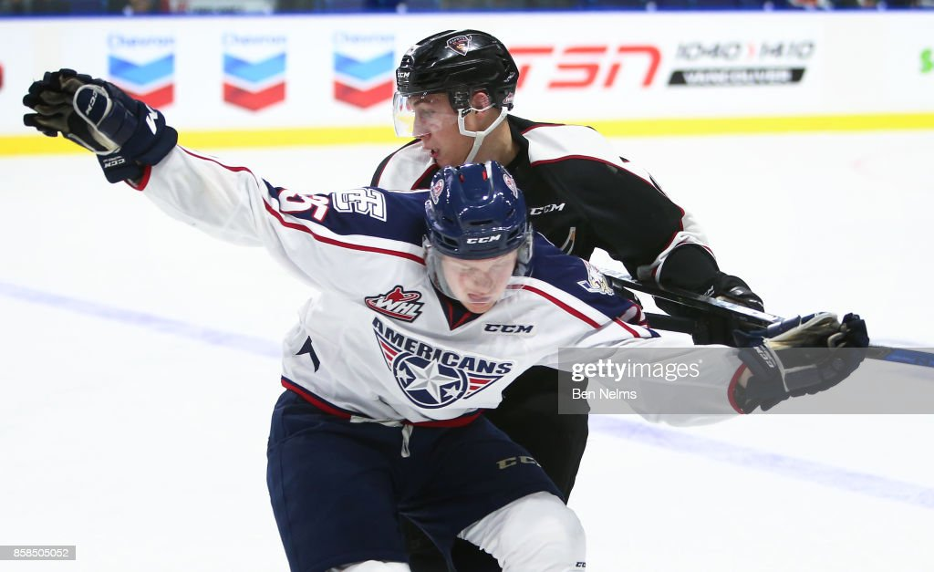 Owen Hardy #15 of the Vancouver Giants checks Kyle Olson #25 of the Tri-City Americans during the third period of their WHL game at the Langley Events Centre on October 6, 2017 in Langley, British Columbia, Canada.