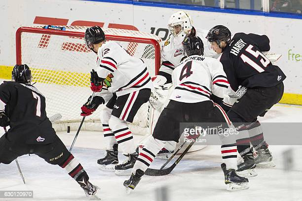 Owen Hardy of the Vancouver Giants slide the puck in the net after goalie Cole Kehler of the Portland Winterhawks got trapped behind his net during...
