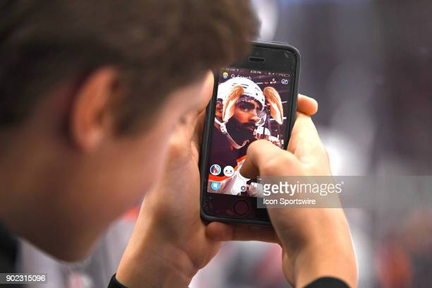 Owen Kmety of Chicago uses his iPhone to put a Snapchat filter on Edmonton Oilers left wing Jujhar Khaira during the second period during a game...