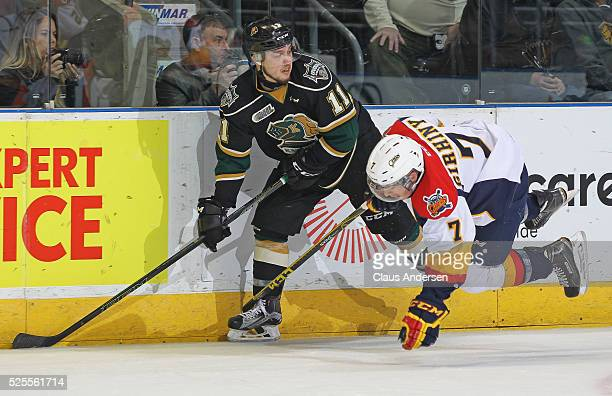 Owen MacDonald of the London Knights slips a puck back past a falling Christian Girhiny of the Erie Otters during game four of the OHL Western...