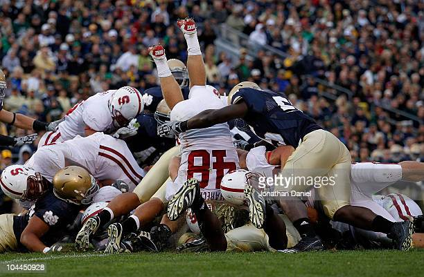 Owen Marecic of the Stanford Cardinal jumps over the line to score an offensive touchdown against the Notre Dame Fighting Irish at Notre Dame Stadium...