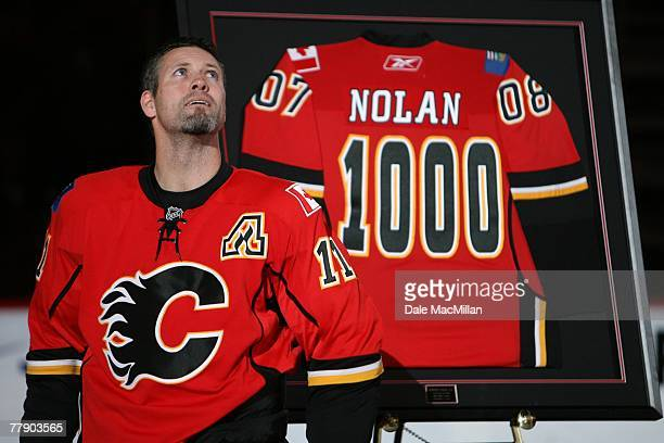 Owen Nolan of the Calgary Flames receives a commemorative jersey for his 1000th game played prior to the NHL game against the San Jose Sharks at the...