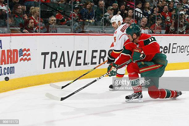 Owen Nolan of the Minnesota Wild and Mark Giordano of the Calgary Flames skate to the puck along the boards during the game at the Xcel Energy Center...