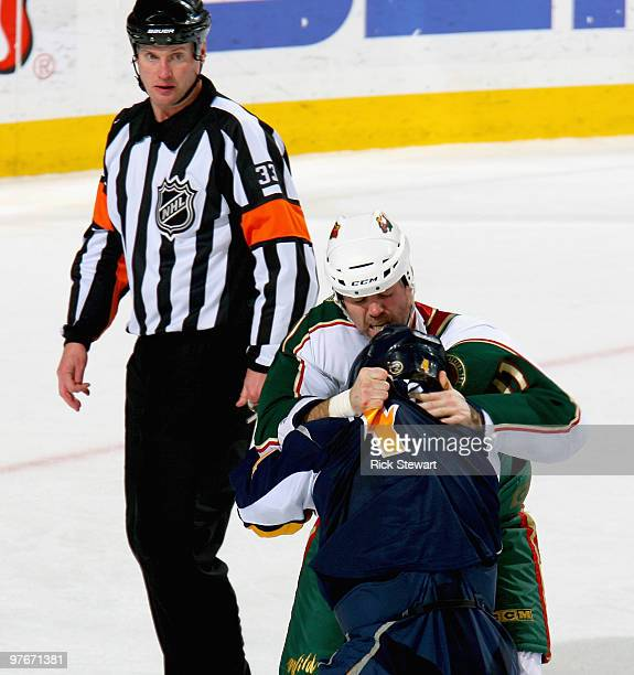 Owen Nolan of the Minnesota Wild and Steve Montador of the Buffalo Sabres fight as referee Kevin Pollock looks on at HSBC Arena on March 12 2010 in...