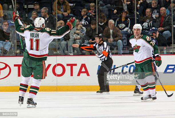 Owen Nolan of the Minnesota Wild congratulates teammate Eric Belanger on scoring a goal against the Nashville Predators at the Sommet Center on...
