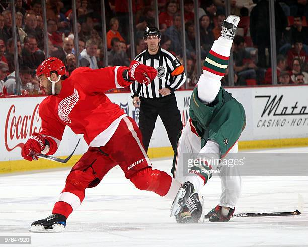 Owen Nolan of the Minnesota Wild gets tripped up by Andreas Lilja of the Detroit Red Wings during an NHL game at Joe Louis Arena on March 11 2010 in...