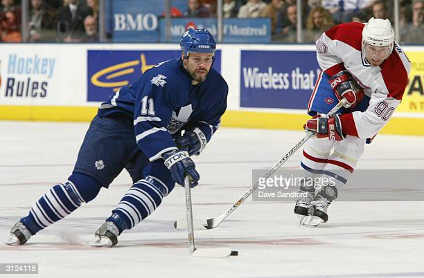 Owen Nolan of the Toronto Maple Leafs skates with the puck ahead of Joe Juneau of the Montreal Canadiens during the game at Air Canada Centre on...
