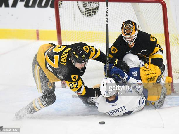 Owen Tippett of the Mississauga Steelheads is brought down by Riley McCourt in front of goalie Kaden Fulcher of the Hamilton Bulldogs during game...